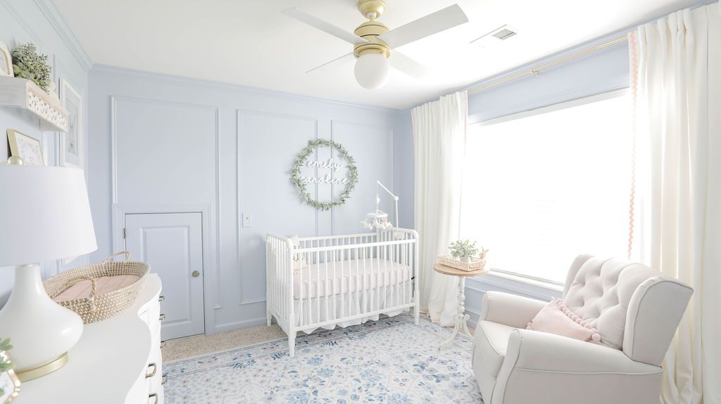 nursery with pale blue walls and white furniture