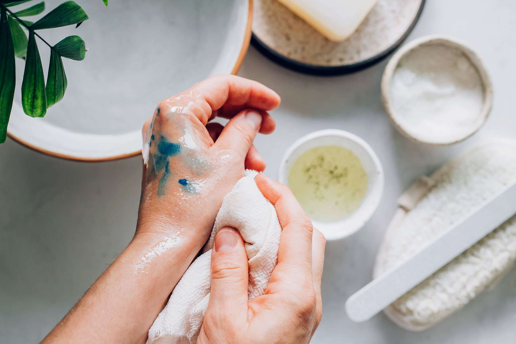 Oil-based paint removed from hand with vegetable oil with white cloth