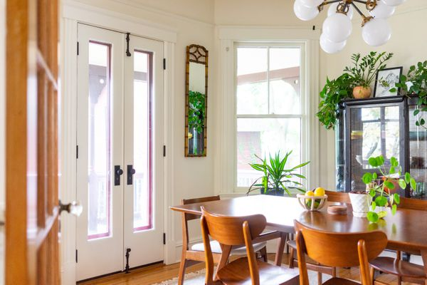 Dining room with wooden table and surrounded by white walls and houseplants