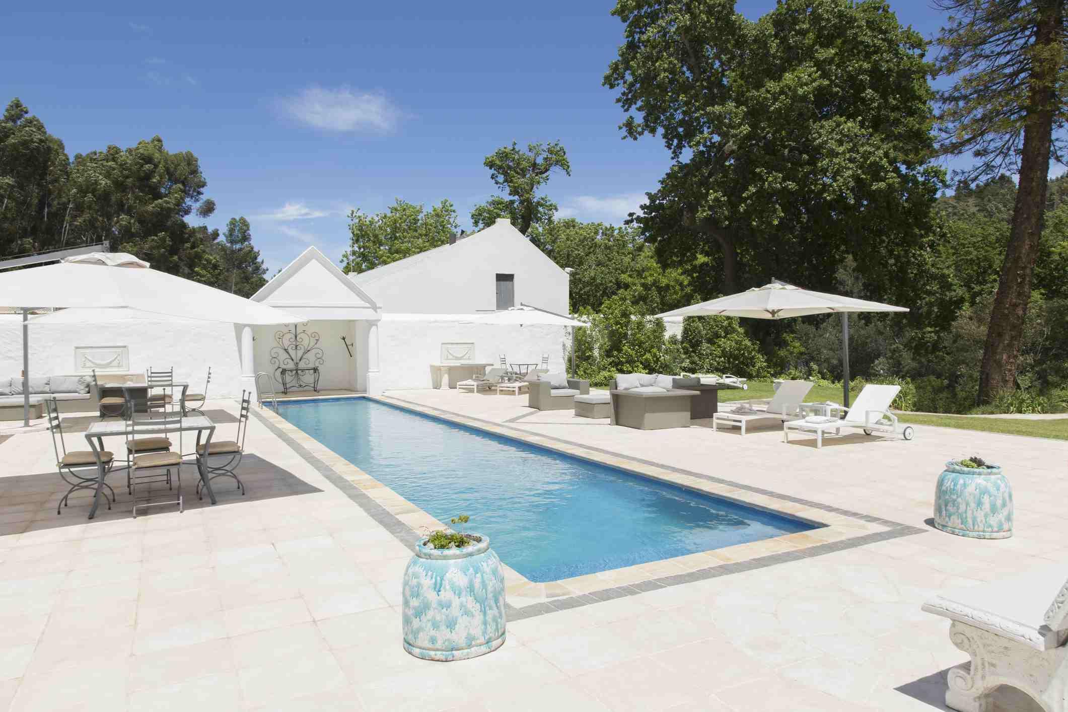 Una piscina de entrenamiento contra azulejos blancos, muebles de patio y blanco sombrillas