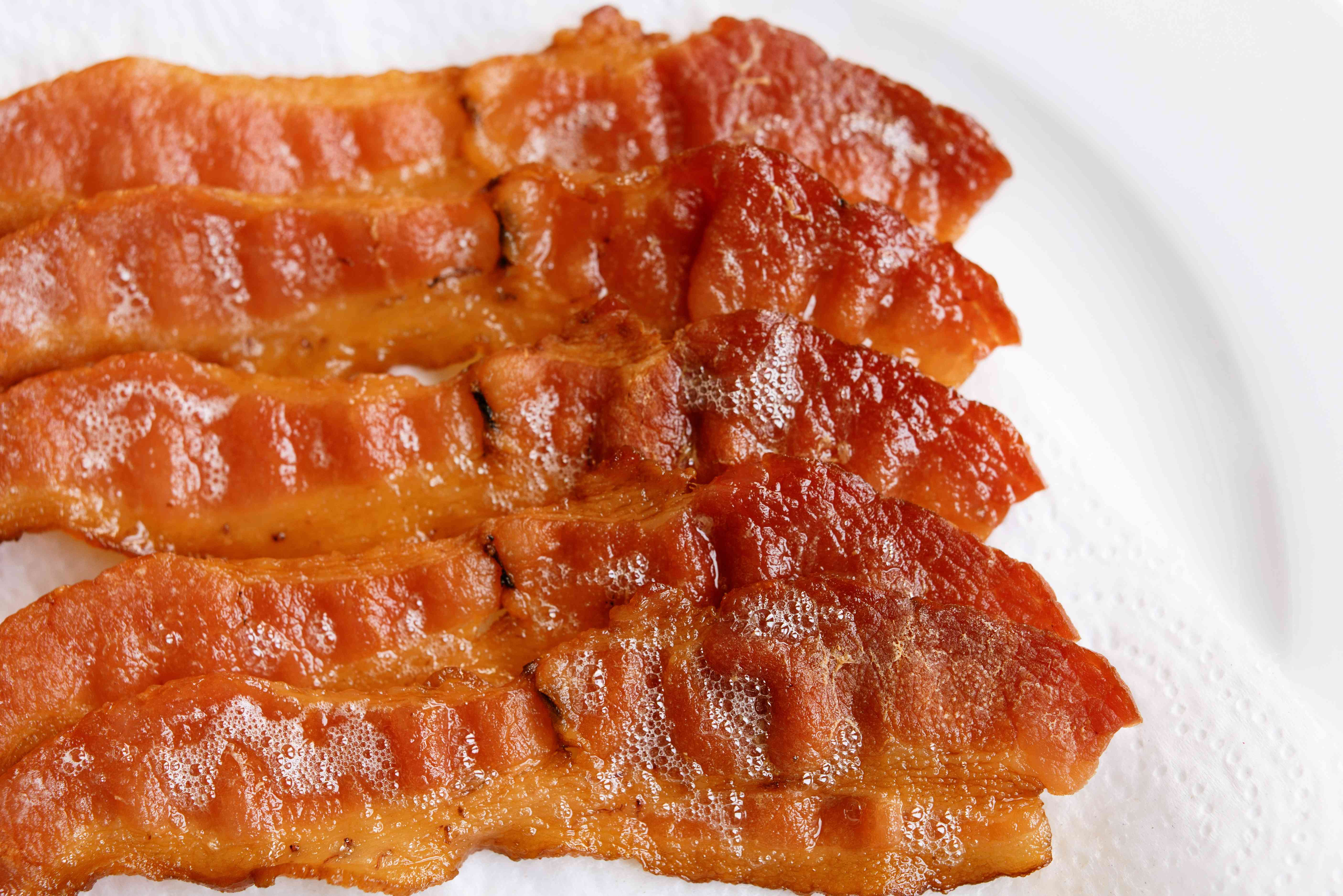 Strips of bacon covered in grease on paper towel and white plate closeup