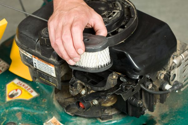 Hand placing an air filter into a lawn mower.