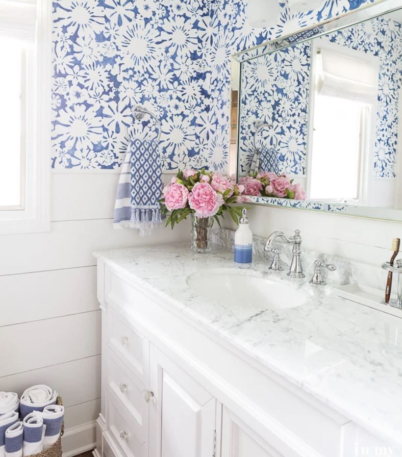 Updated bathroom with blue and white wallpaper and marble topped vanity.
