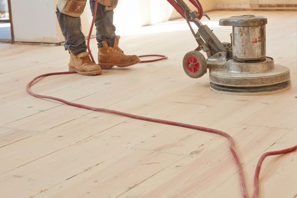 Drum sander passing over hardwood floor with orange cord hanging across floor