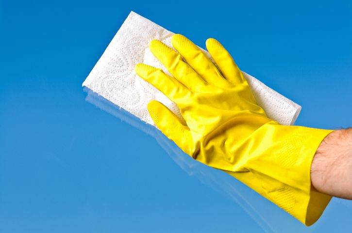 Gloved hand wiping glass window