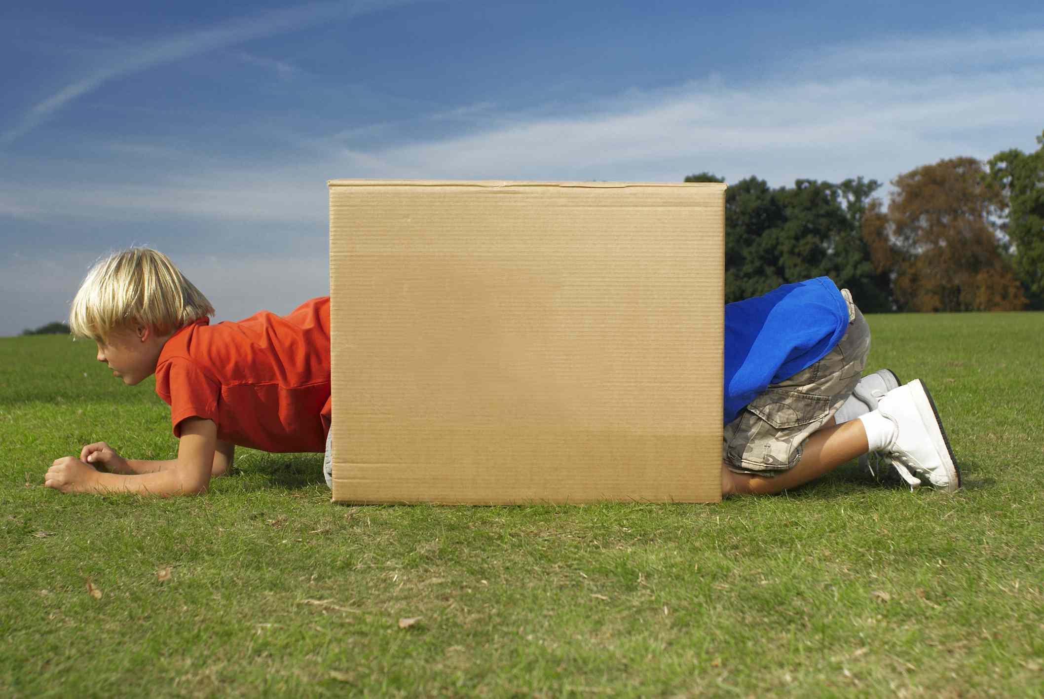 Two kids crawling through a cardboard box