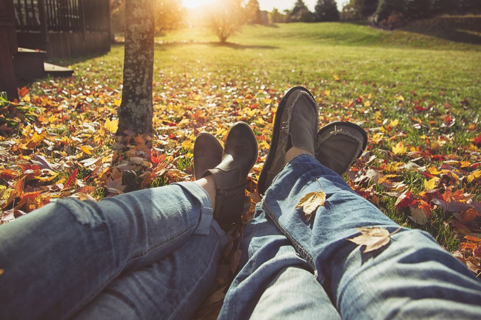Couple relaxing on lawn in fall with leaves.