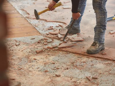 Ceramic floor tiles being removed with a masonry chisel and floor scraper by hand