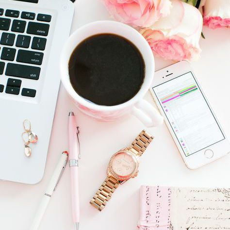 A work desk with coffee and flowers