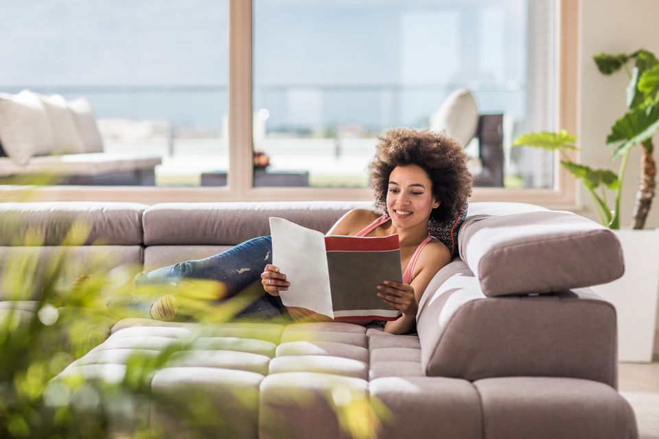 Happy African American woman relaxing on sofa in the living room and reading a magazine.