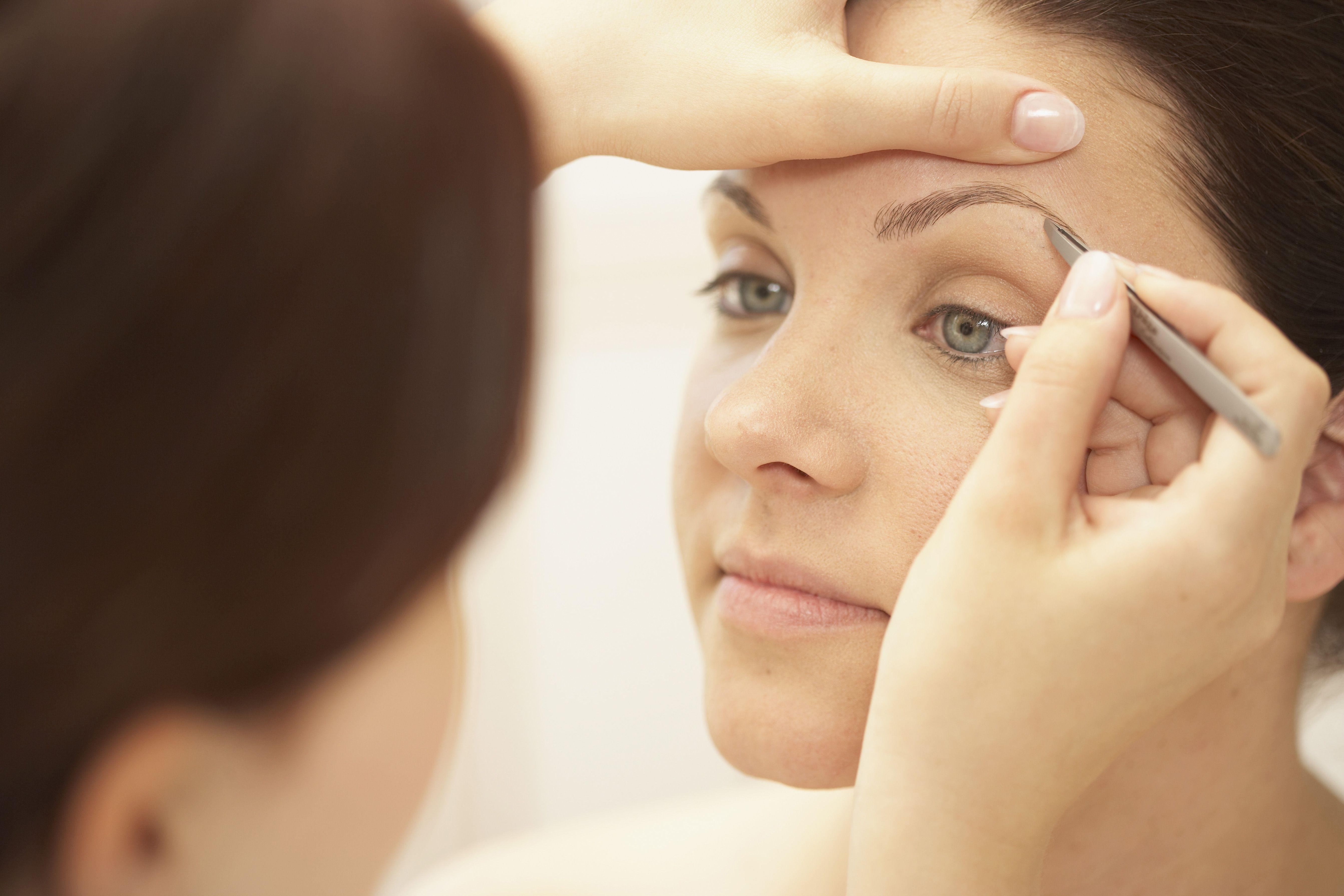 Women plucking eyebrows in spa