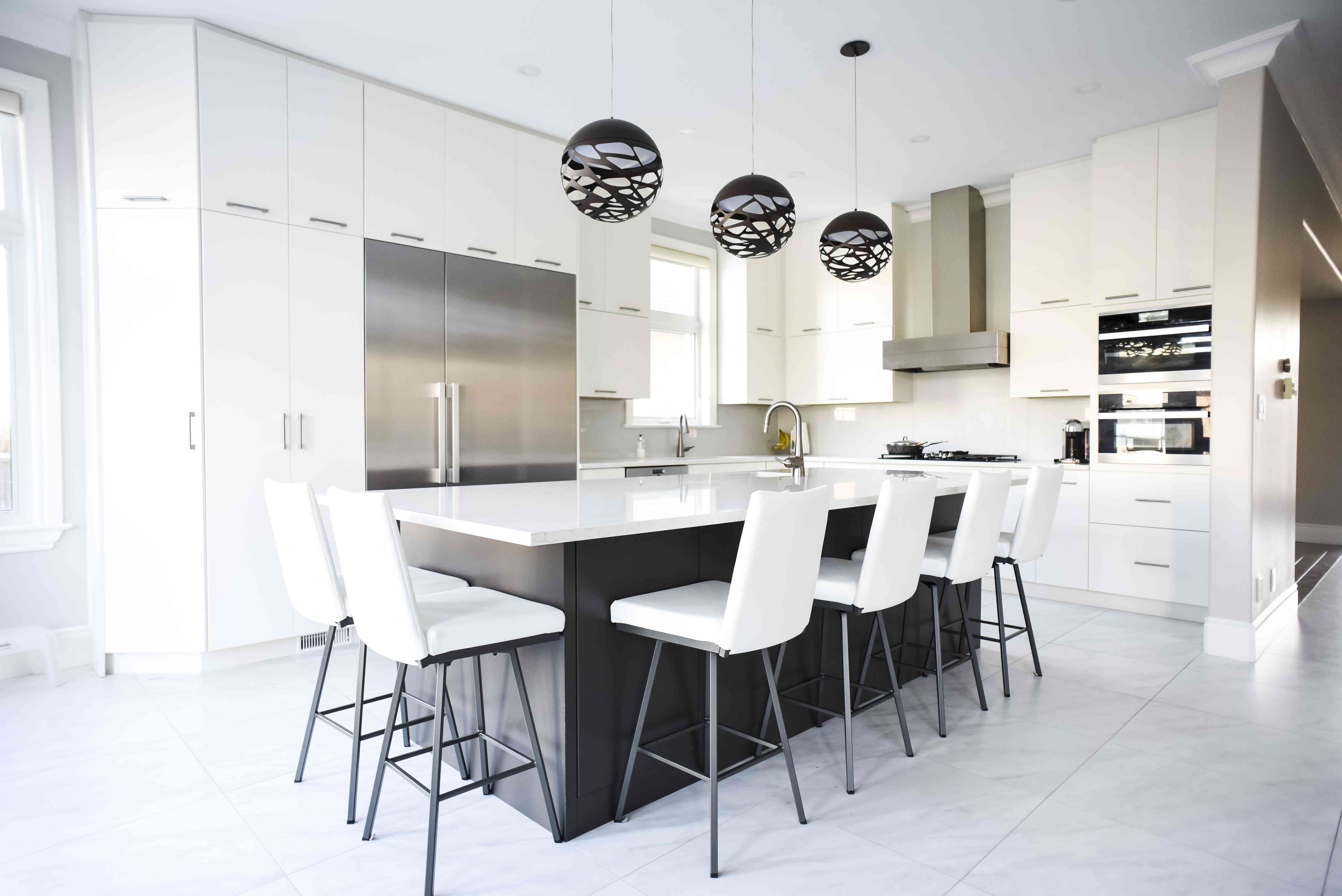 Modern white kitchen with large island and stainless steel appliances.