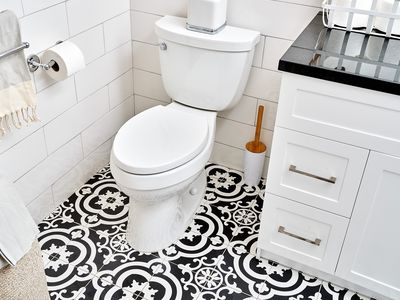 Standard gravity-flush toilet surrounded by black and white patterned tile floor in bathroom