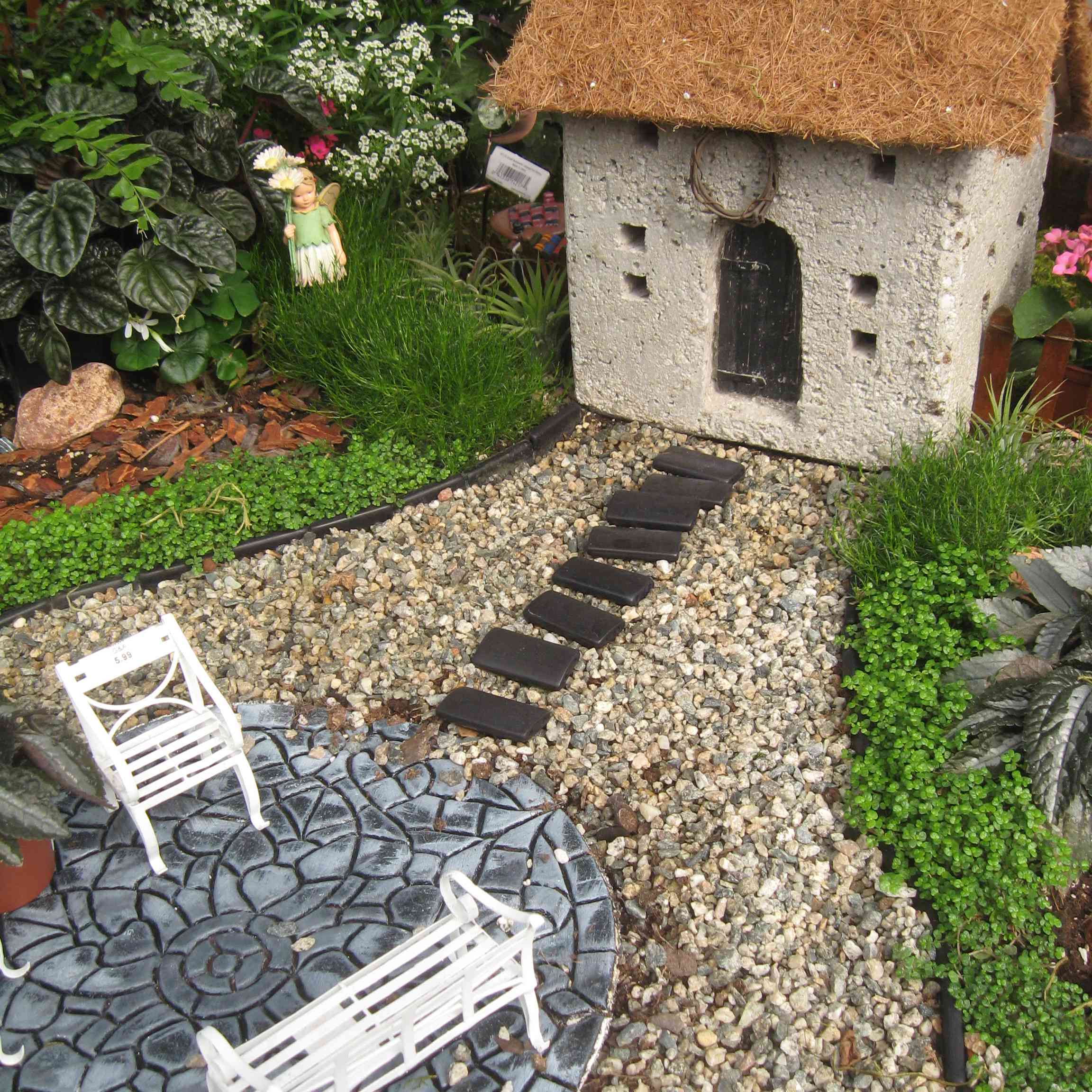 Miniature house and furniture in fairy garden.