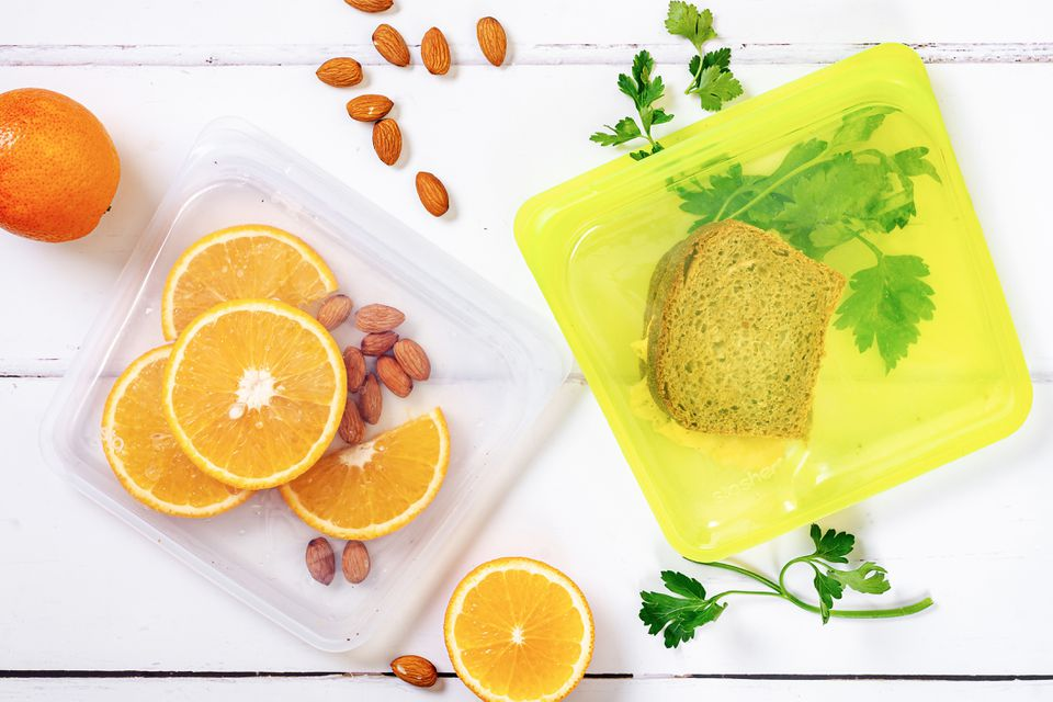 Reusable food storage bags with orange slices and almonds and sandwich with cilantro