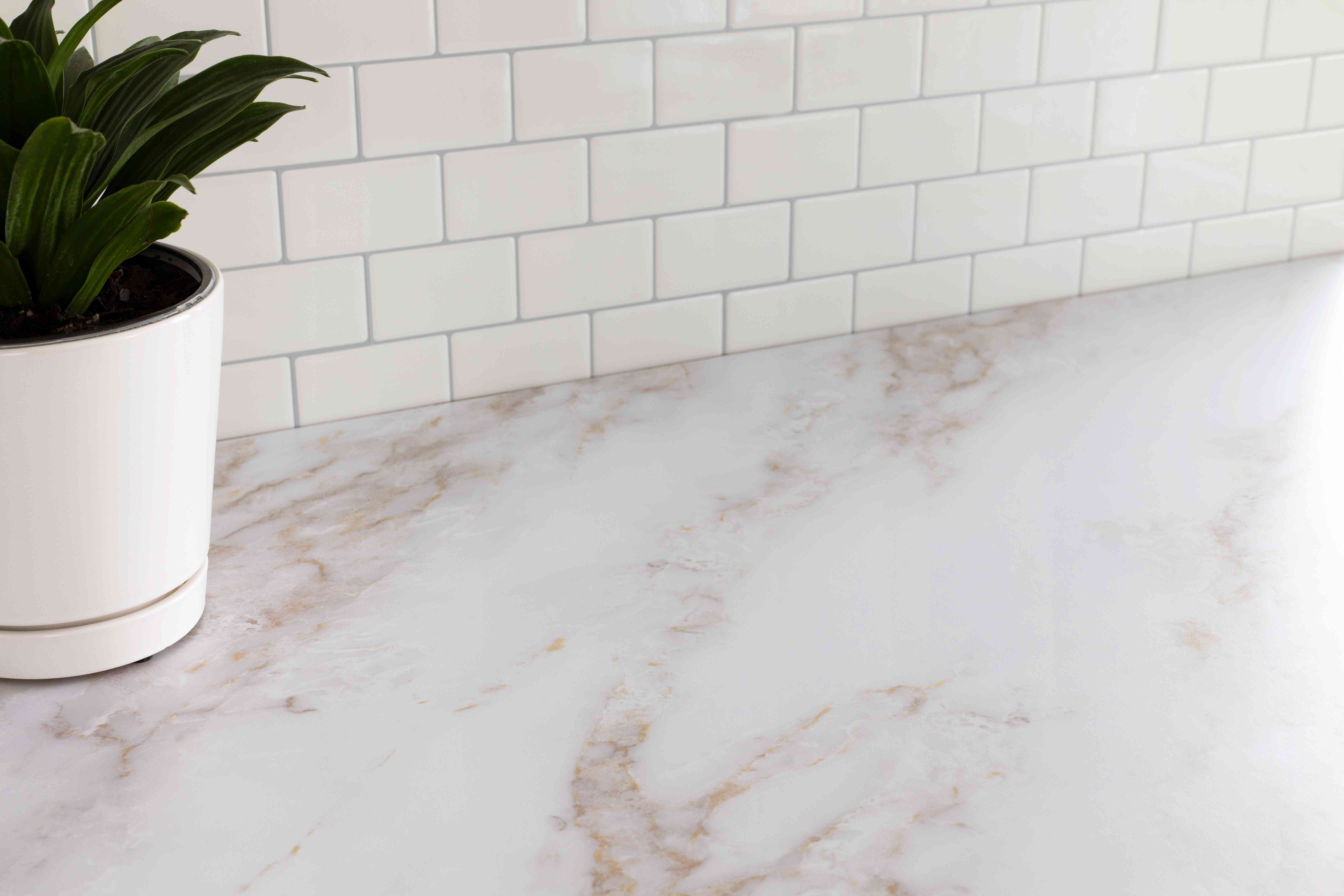 White marbled flat surface to fold towels with houseplant