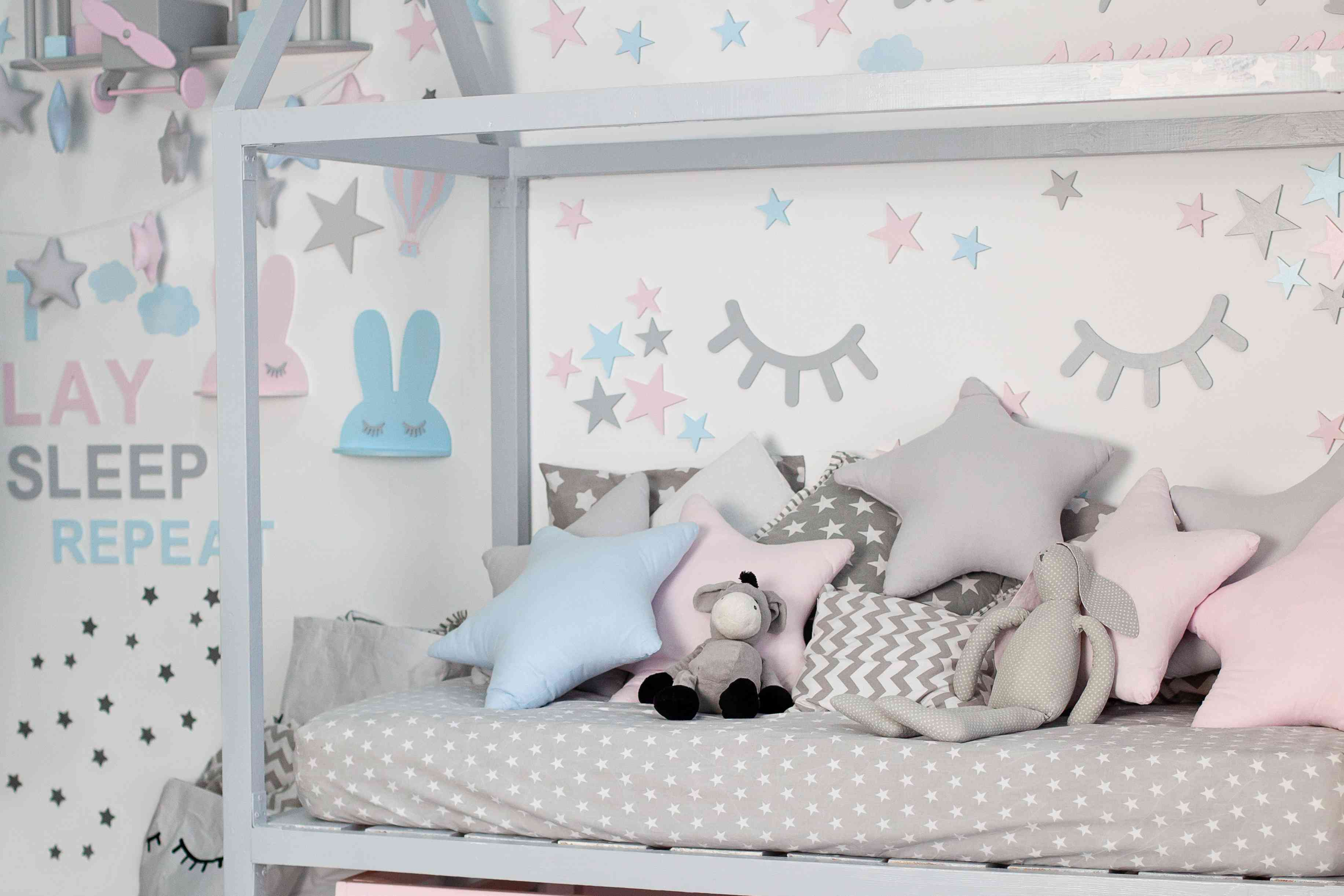 Kids bed in white sunny bedroom. Children room and interior design. Bed for baby or toddler boy at home. Bedding and textile for children nursery. Nap and sleep time. Children bedroom with pillows.