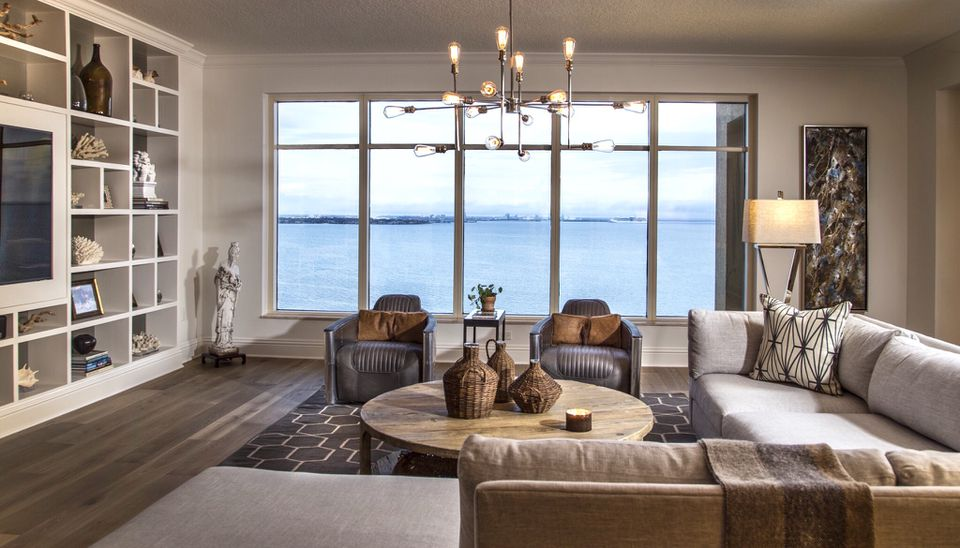 A neutral brown and gray living room with a view of water. The room follows the 60-30-10 rul