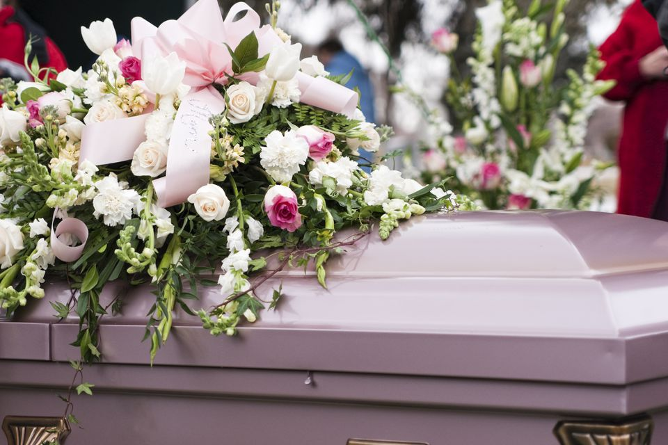 pink casket with flowers on top