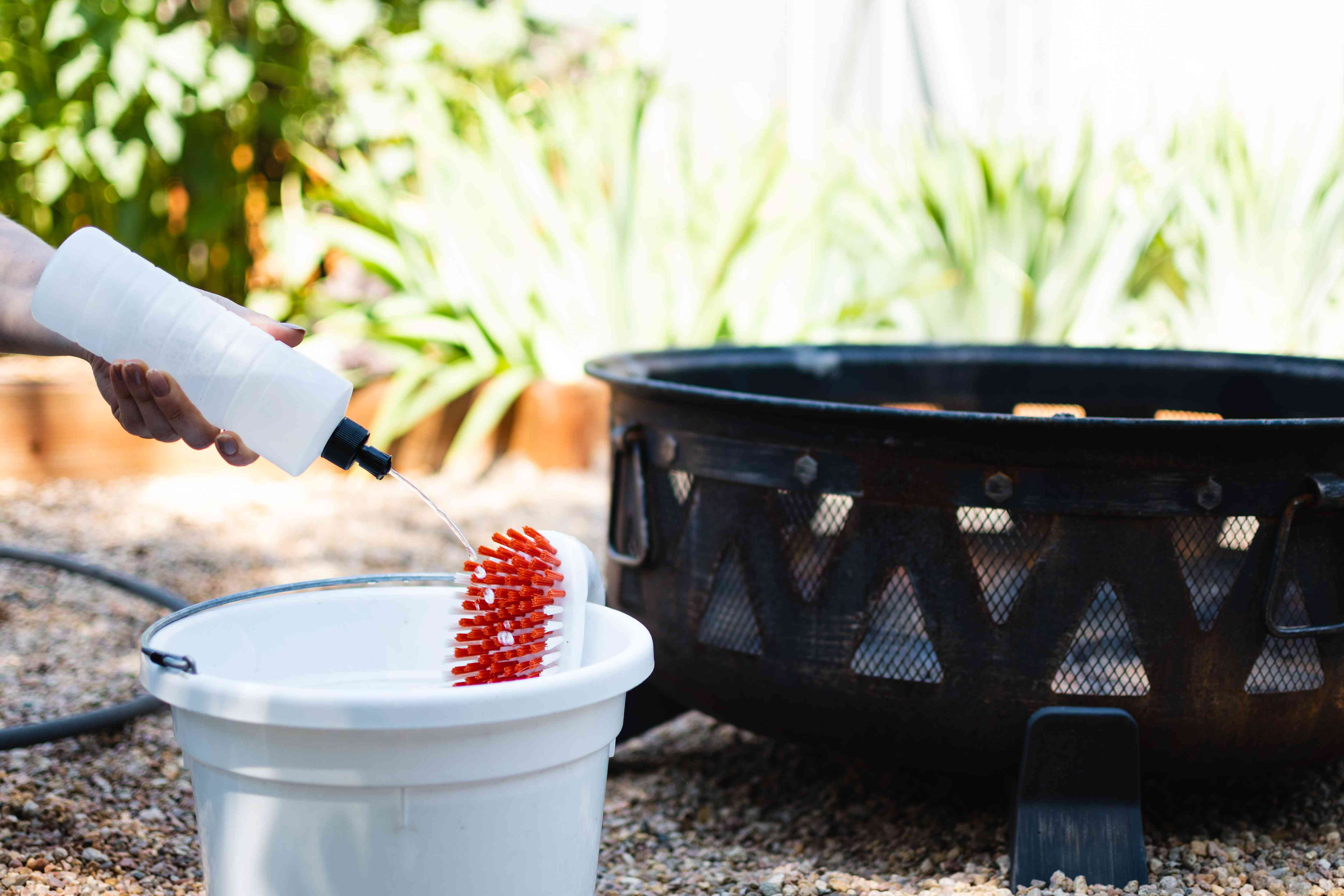 Dishwashing liquid and water poured in white bucket with red scrub brush next to metal fire pit