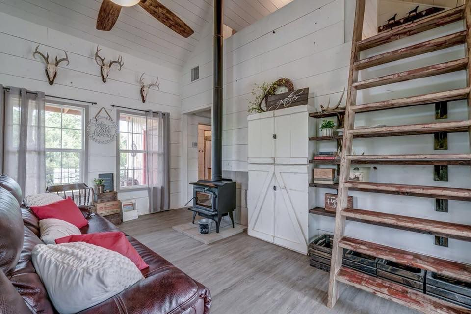 A tiny home with a leather couch, wood paneling and deer antlers on the wall
