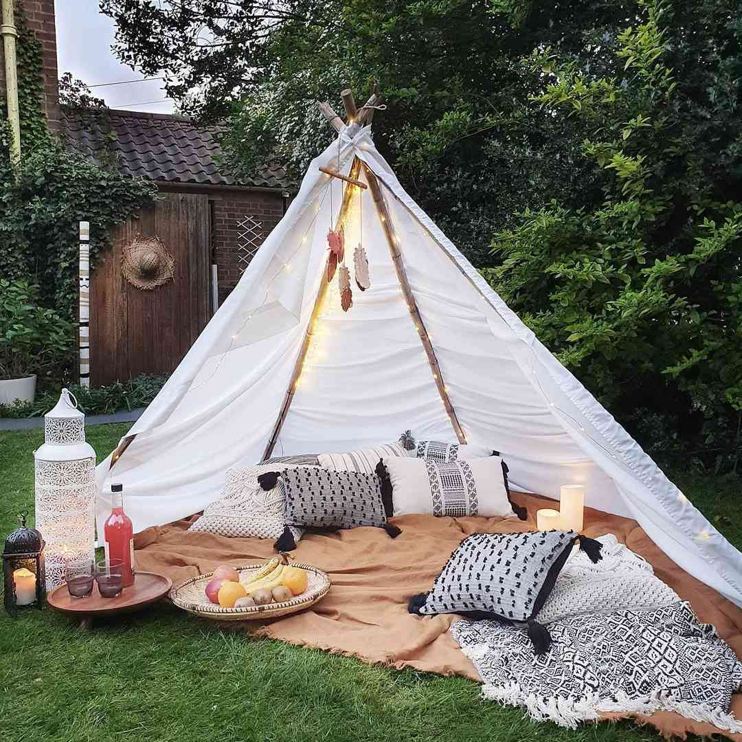 An outdoor teepee with blankets, pillows and a fruit bowl.