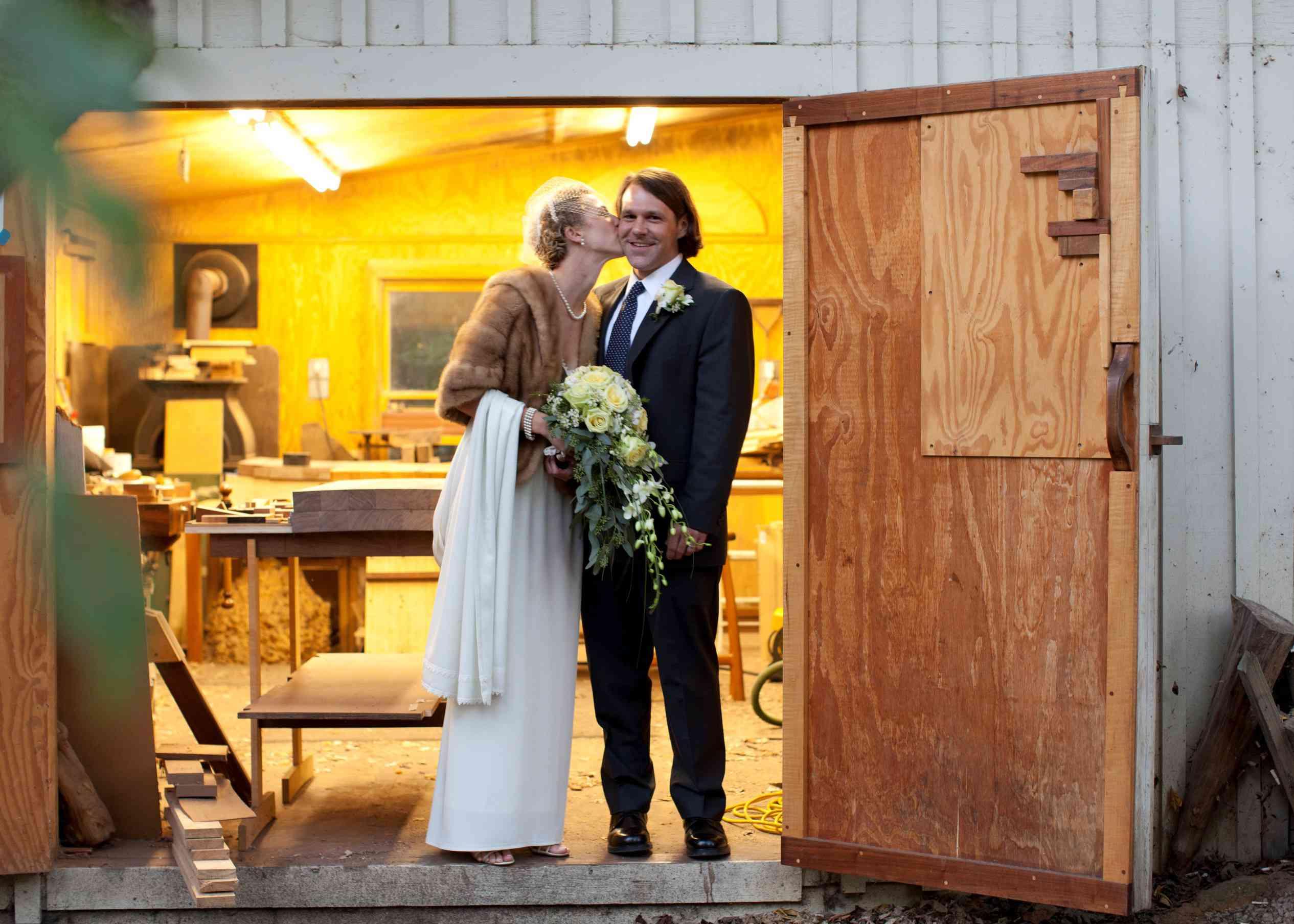 Katie and Joseph's wedding, standing in the doorway of their workshop