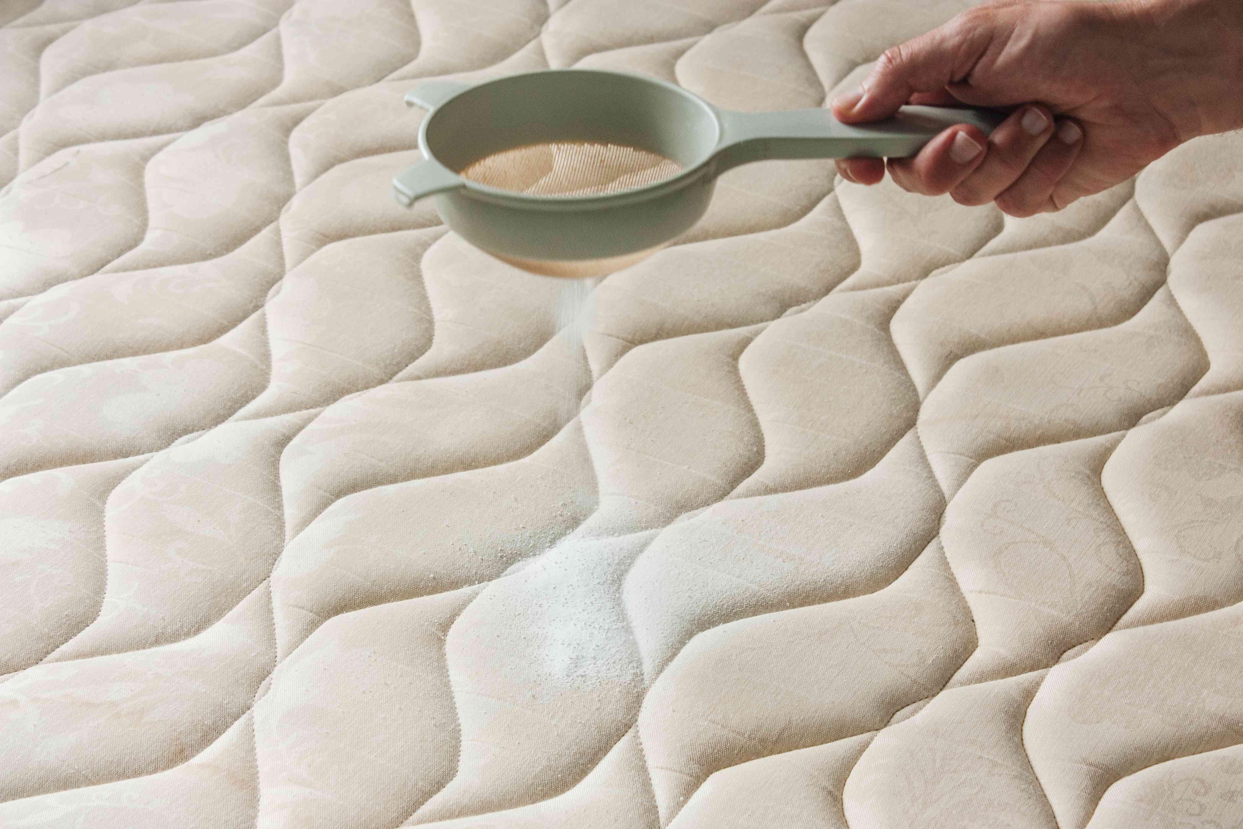 person sprinkling baking soda onto a mattress