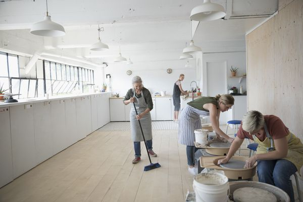 Female potters cleaning pottery wheels and sweeping floor in art studio