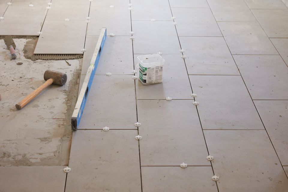 Underlayment exposed to the left of ceramic tile floor with level and hammer on top