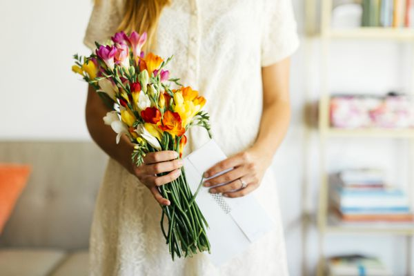 Woman holding bouquet and letter