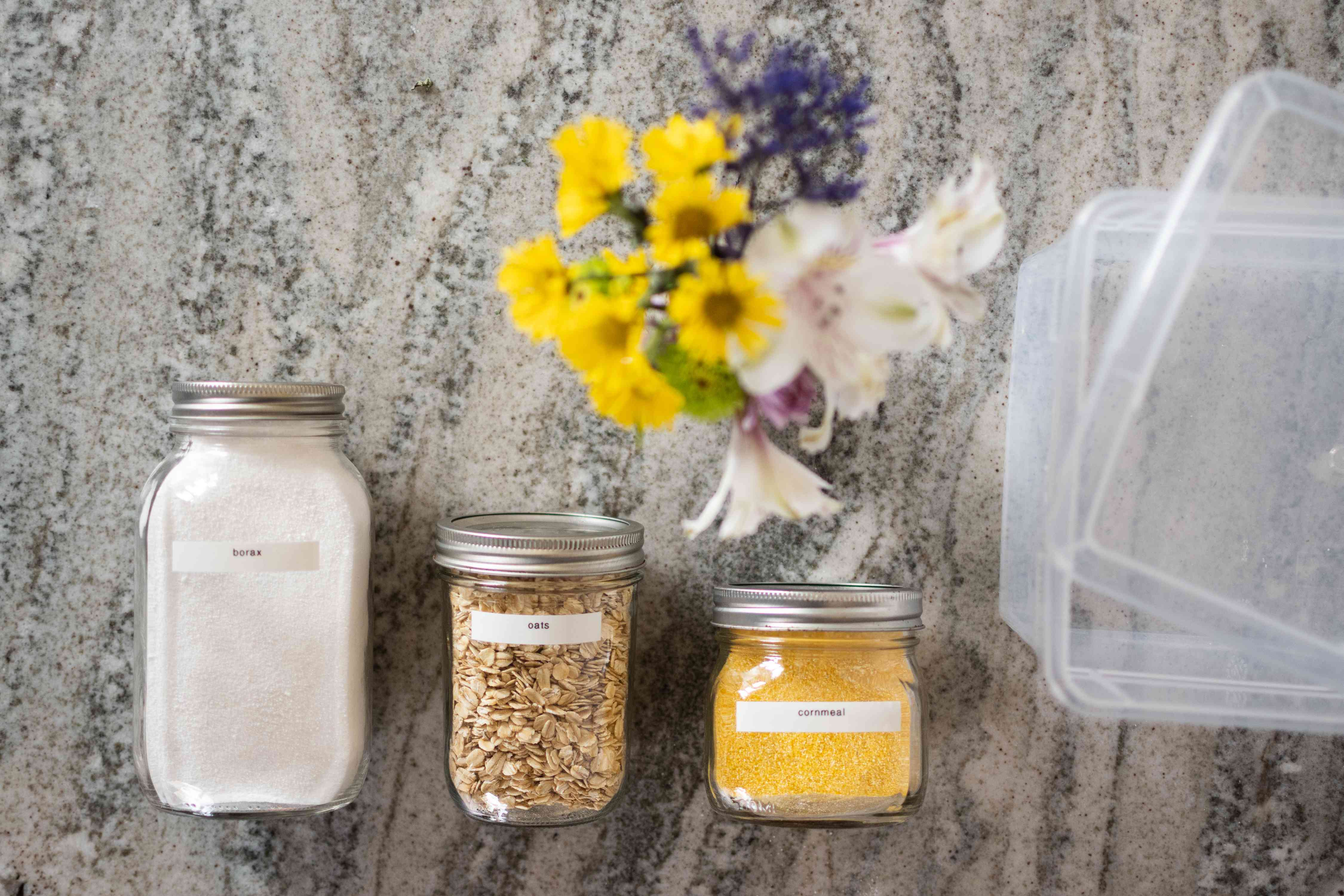 Three glass jars with ingredients to dry flowers next to plastic bin and flowers