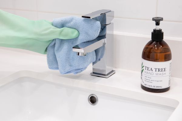 Chrome sink faucet cleaned with blue microfiber cloth next to bottle of tea tree hand wash
