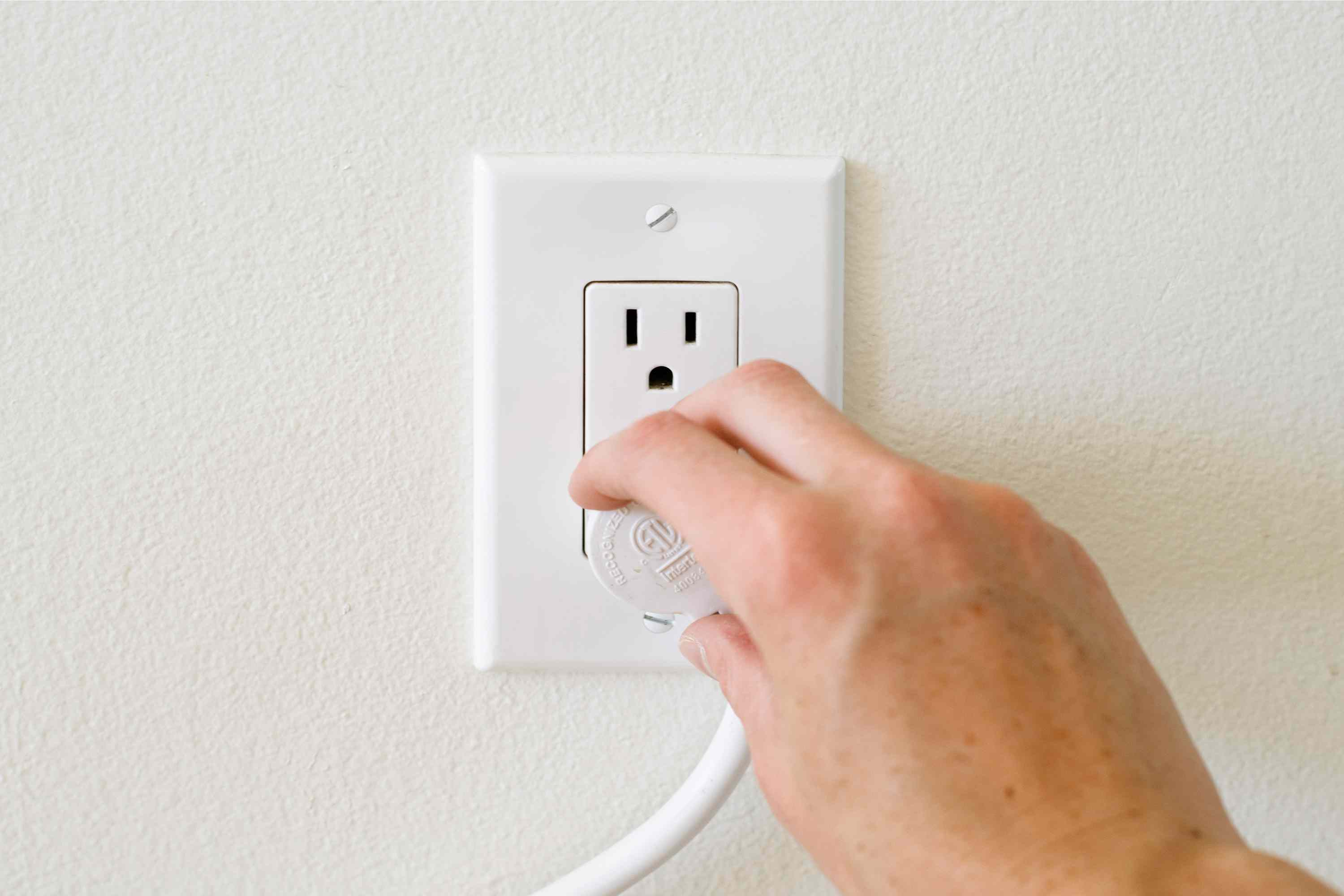 Power cord to refrigerator being checked on wall outlet