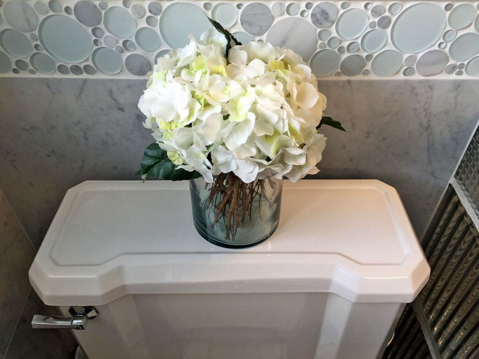 The top of a toilet with fresh flowers