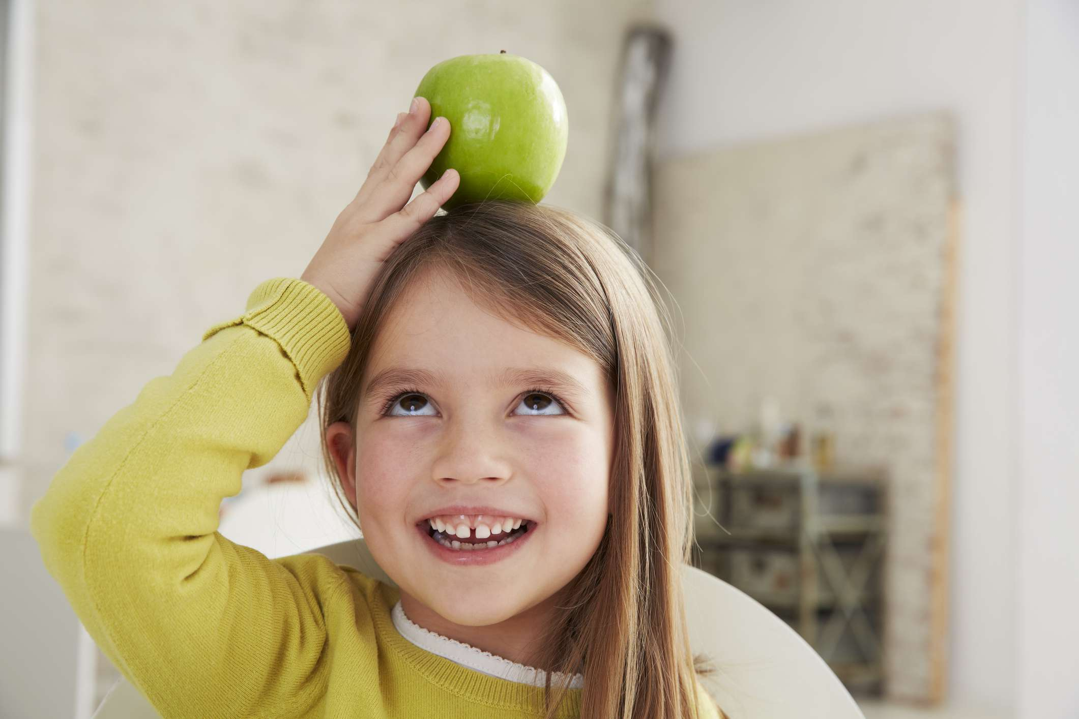 Young girl balancing an apple on her head