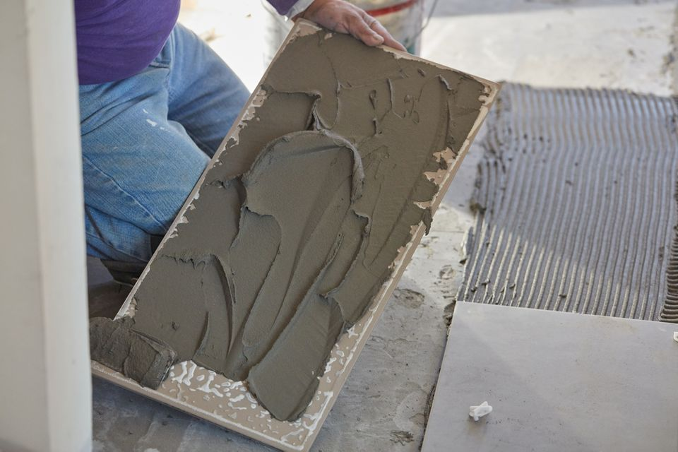 Gray flooring adhesive applied under ceramic tile