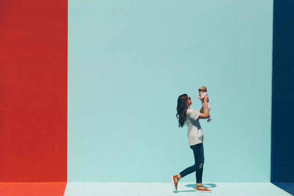 Woman holding baby up in front of an aqua and red wall