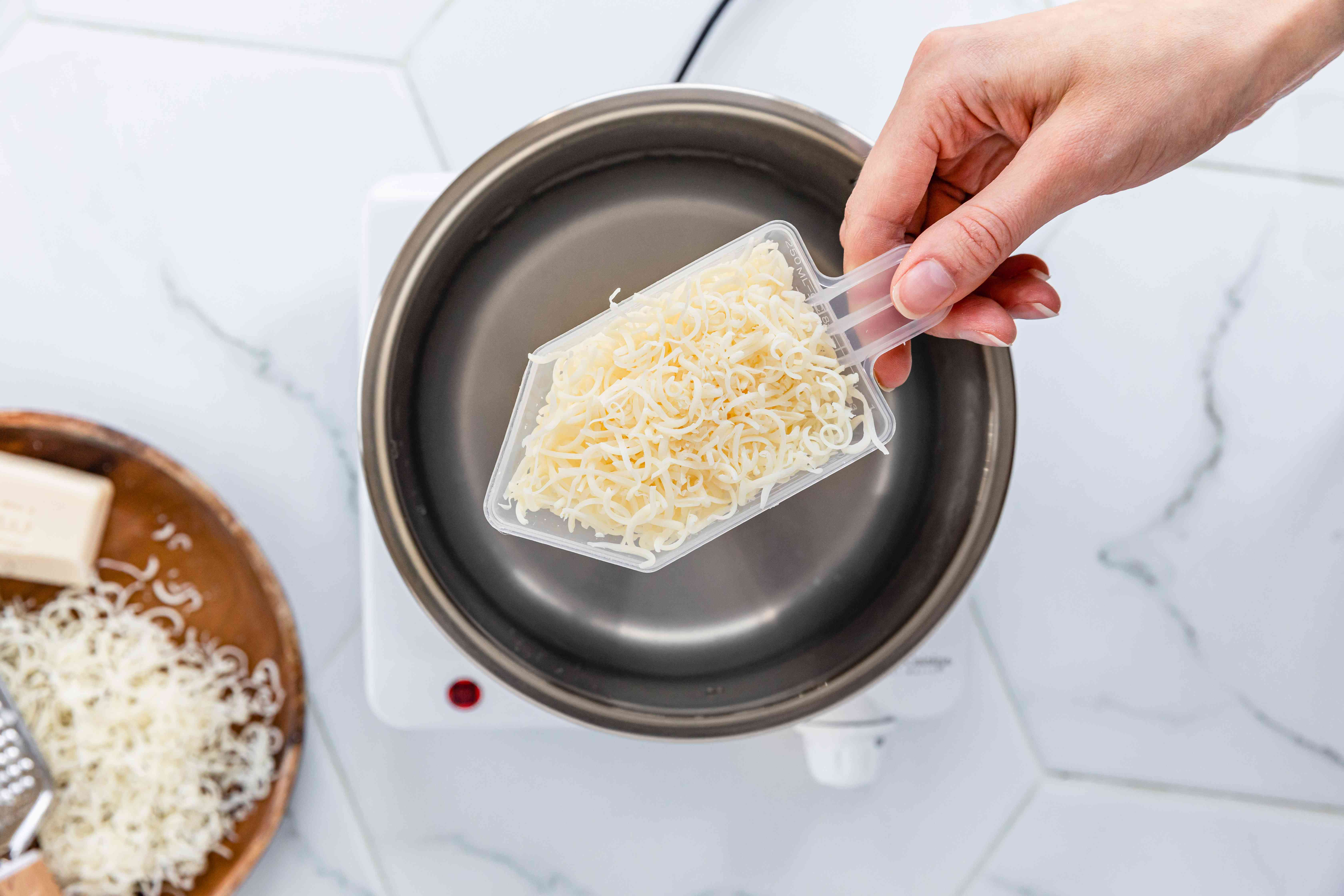 DIY liquid laundry detergent with grated soap in plastic scoop over saucepan