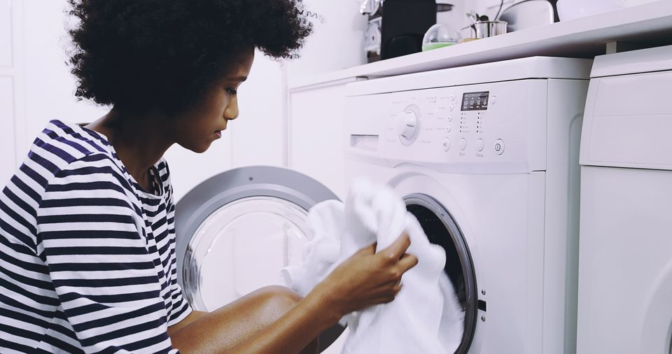 Woman loading clothing into the dryer