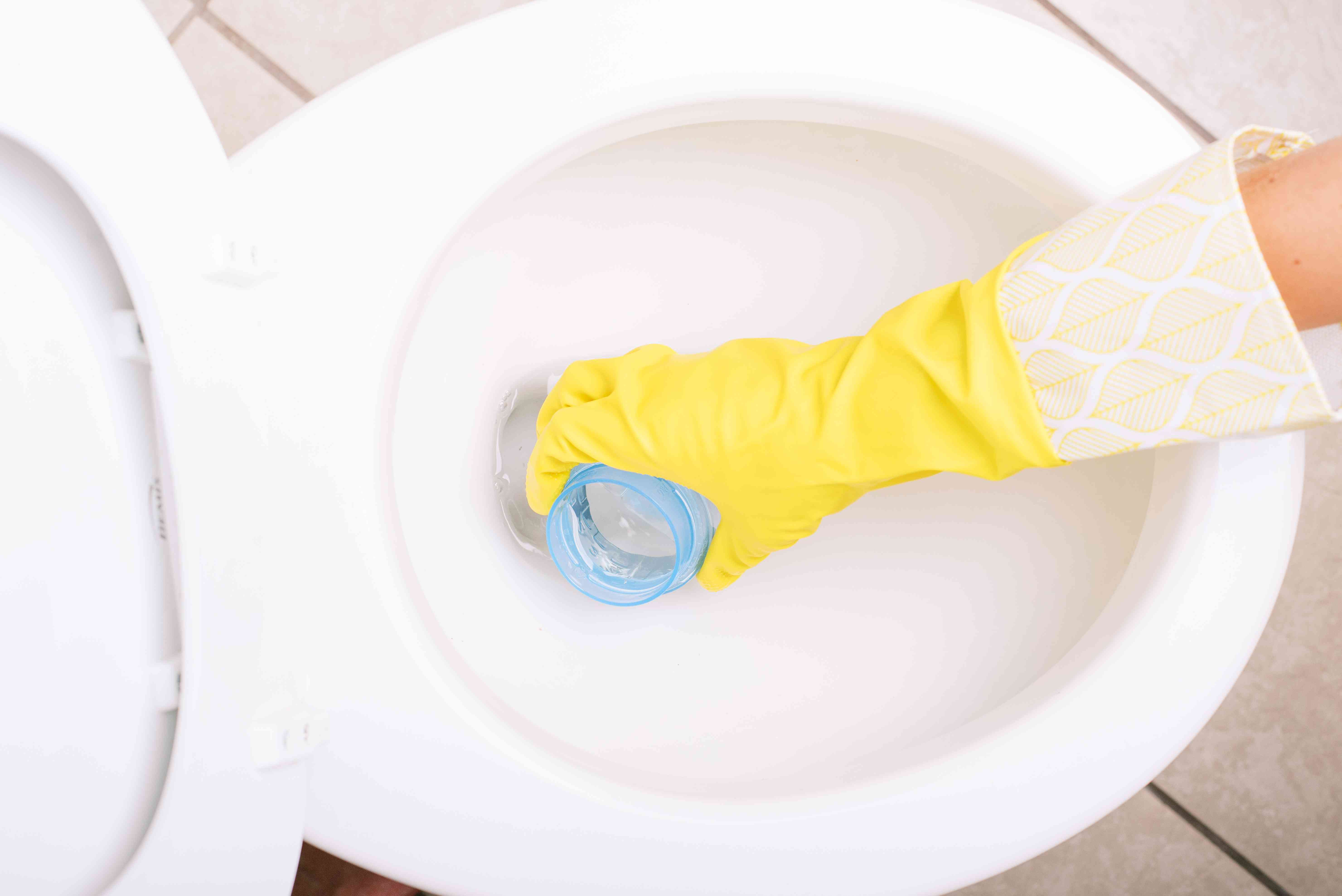 White ceramic toilet bailing out water with laundry bottle cap and yellow gloves