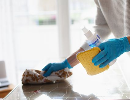Woman cleaning table with disinfectant spray, close-up of hands in protective gloves - stock photo