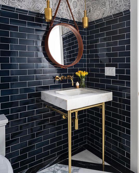 Baño con azulejos de color azul marino oscuro y adornos dorados