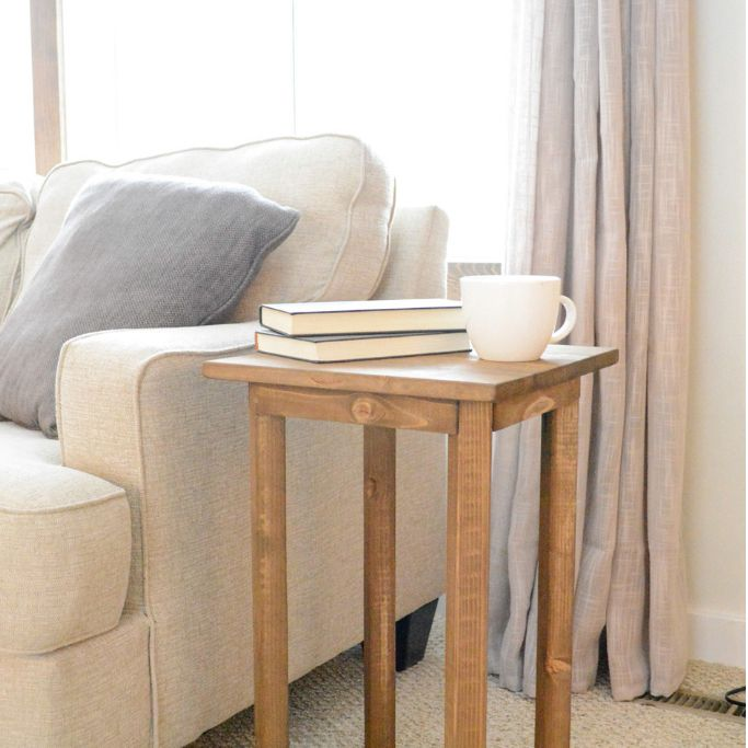 A wooden end table by a window and couch