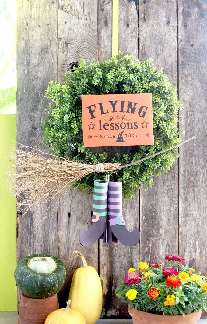 A wreath with witches legs and a broom