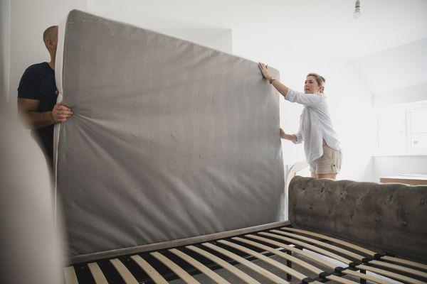 A couple moving a mattress.