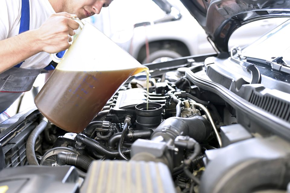 Car mechanic refilling engine oil