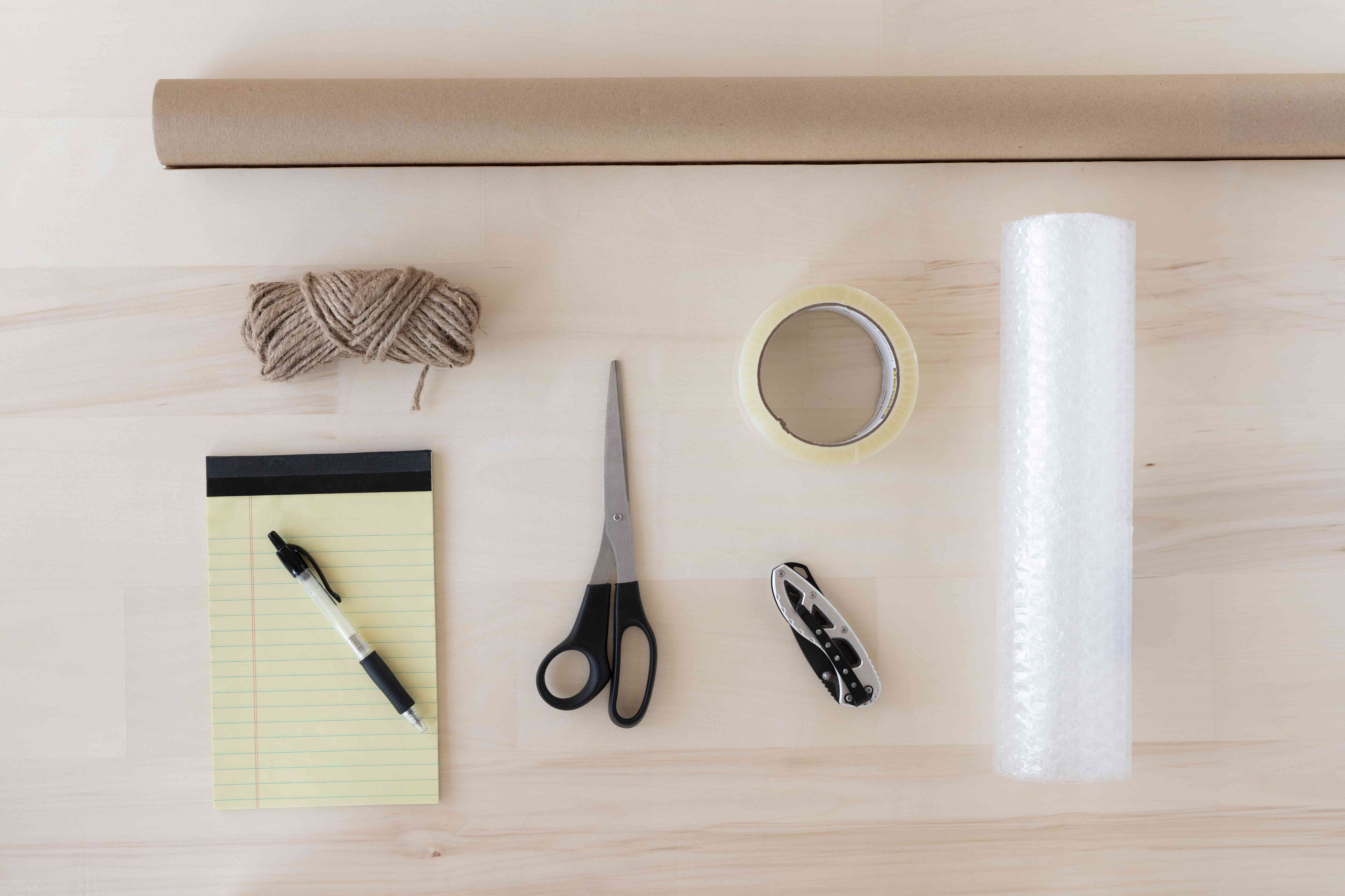 Packing supplies with scissors, notepad, bubble wrap, kraft paper, string and tape on table