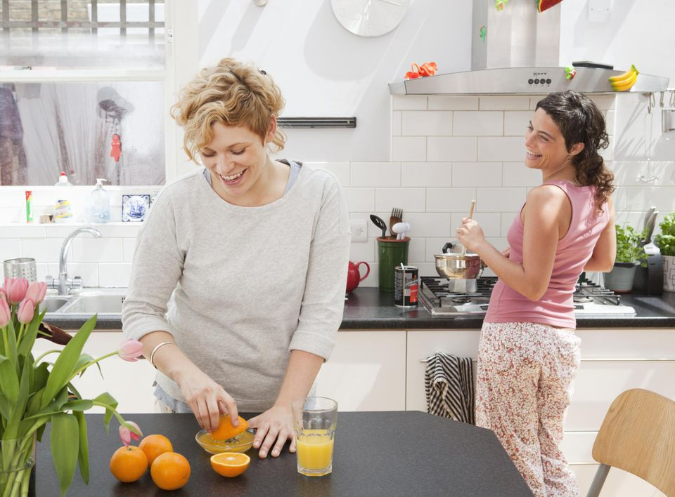 Female friends making breakfast in kitchen