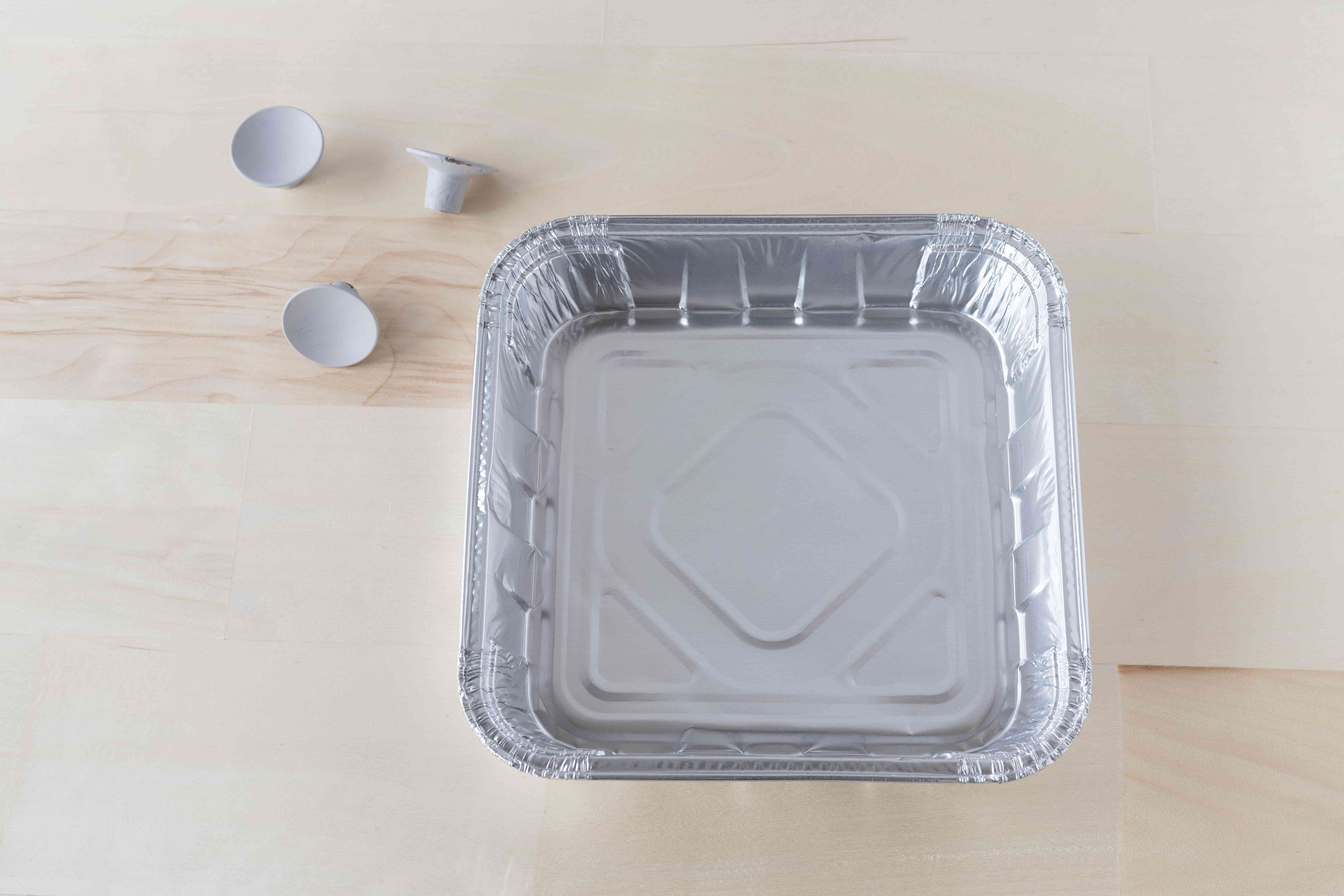 Disposable aluminum tray next to painted metal knobs on wood surface